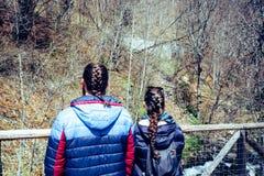 Acople em uma ponte que olha o rio nos amantes da floresta de trás com trança fotografia de stock royalty free