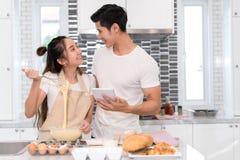 Acople a fatura da padaria, do bolo na sala da cozinha, do homem asiático novo e da mulher junto imagens de stock