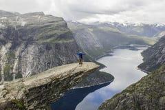 Acople fazer titânico na rocha da língua do ` s da pesca à corrica do trolltunga, Noruega foto de stock