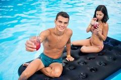 Acople a flutuação em um colchão inflável na piscina, em cocktail bebendo e em divertimento ter em suas férias de verão Foto de Stock