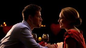 Acople guardar as mãos e admirar-se na data romântica no restaurante imagens de stock royalty free