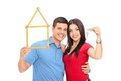 Acople guardar a fita métrica no formulário da casa e da chave Fotos de Stock Royalty Free
