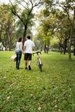 Acople manter a mão e andar unida no parque fotografia de stock royalty free
