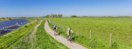 Acople a montada de sua bicicleta ao longo do rio de Reitdiep em Groninge Imagem de Stock Royalty Free