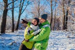 Acople no amor que anda e que abraça nos jovens da floresta do inverno que têm apontar e olhar algo imagens de stock royalty free