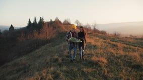 Acople no amor que caminha fora Caminhantes homem e passeio trekking da mulher com as trouxas na fuga com o mapa no por do sol de video estoque