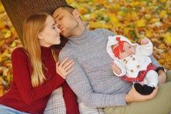 Acople no amor que senta-se nas folhas caídas outono em um parque, sente-se perto de uma árvore, apreciando um dia bonito do outo foto de stock royalty free