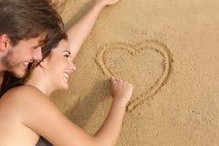 Acople no amor que tira um coração na areia da praia imagens de stock royalty free