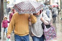 Acople o abrigo sob o guarda-chuva na chuva pesada no, Reino Unido Imagens de Stock Royalty Free