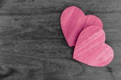 Acople o amor cor-de-rosa dos corações de madeira no fundo de madeira da tabela imagem de stock