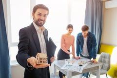 Acople o apartamento da compra ou do aluguel junto Homem no brinquedo de madeira pequeno da posse do terno à disposição e mostra  fotos de stock