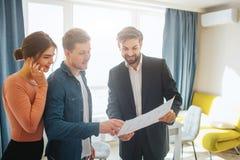 Acople o apartamento da compra ou do aluguel junto Plano da posse do corretor de imóveis e do homem junto e para olhá-lo Suporte  imagem de stock