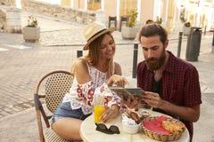 Acople o assento e a leitura do guia na cafetaria, Ibiza, Espanha Imagem de Stock