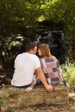 Acople o assento em um banco de pedra na natureza Imagem de Stock