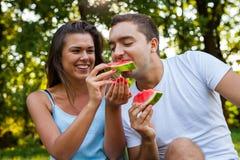 Acople o assento em uma cobertura do piquenique e comer a melancia Imagem de Stock Royalty Free