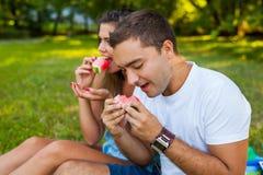 Acople o assento em uma cobertura do piquenique e comer a melancia Imagens de Stock Royalty Free