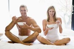 Acople o assento na cama que come o cereal e o sorriso Fotografia de Stock Royalty Free