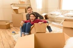 Acople o assento no assoalho com as caixas na casa nova foto de stock royalty free