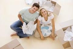 Acople o assento no assoalho por caixas abertas na HOME nova imagens de stock royalty free