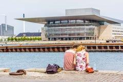 Acople o assento no cais na frente do Copenhaga Opera fotografia de stock