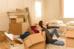 Acople o assento no cardbox e no assoalho na casa nova foto de stock royalty free