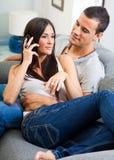 Acople o assento no sofá e a fala no telefone Imagens de Stock Royalty Free