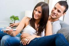 Acople o assento no sofá e na televisão de observação a Fotos de Stock
