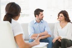 Acople o assento no sofá que fala com seu terapeuta Foto de Stock Royalty Free