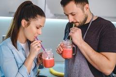 Acople o batido bebendo com uma palha na cozinha imagens de stock royalty free