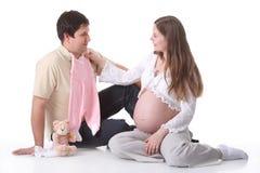 Acople o bebê de espera que olha na roupa do bebê Imagem de Stock Royalty Free