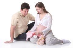 Acople o bebê de espera que olha na roupa do bebê Imagens de Stock