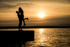 Acople o beijo na praia com um por do sol bonito Foto de Stock