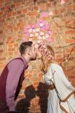 Acople o beijo nos corações da máscara da parede do fundo Fotografia de Stock