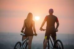 Acople o ciclista com os Mountain bike no monte no por do sol Fotos de Stock