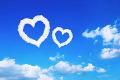 acople o coração branco nuvens dadas forma no céu azul Foto de Stock