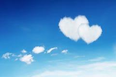 acople o coração branco nuvens dadas forma no céu azul Fotos de Stock