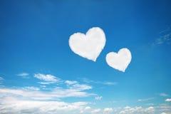 acople o coração branco nuvens dadas forma no céu azul Fotografia de Stock