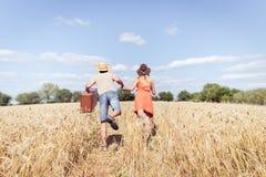 Acople o corredor no campo, homem que realiza em sua mala de viagem do vintage da mão no fundo do céu azul da paisagem do campo f Foto de Stock