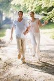Acople o corredor que prende ao ar livre as mãos e o sorriso Fotografia de Stock Royalty Free