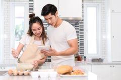 Acople o cozimento da padaria na sala da cozinha, no homem asiático novo e na mulher junto fotografia de stock