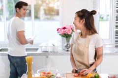 Acople o cozimento do alimento na sala da cozinha, no homem asiático novo e na mulher junto fotografia de stock