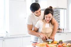 Acople o cozimento do alimento na sala da cozinha, no homem asiático novo e na mulher junto imagens de stock