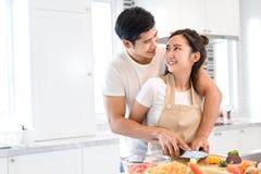 Acople o cozimento do alimento na sala da cozinha, no homem asiático novo e na mulher junto fotos de stock