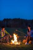 Acople o cozinheiro pelo campo romântico da noite da fogueira Fotos de Stock Royalty Free