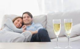 Acople o descanso em um sofá com as flautas do champanhe Fotografia de Stock