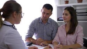 Acople o doutor de visita na clínica de fertilidade, o marido e a esposa na consulta do médico em uma sala médica filme