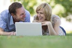 Acople o encontro na grama com o portátil no parque Foto de Stock Royalty Free