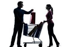 Acople o homem da mulher com a silhueta do carrinho de compras e dos presentes Foto de Stock
