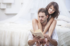 Acople o homem e a mulher em casa na cama com um livro e uma bebida quente Fotografia de Stock
