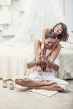 Acople o homem e a mulher em casa na cama com um livro e uma bebida quente Fotos de Stock Royalty Free
